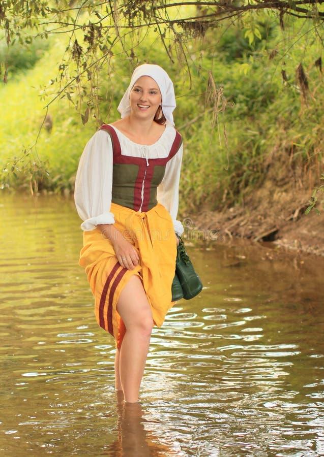 Meisje in historische kleding in water stock foto's
