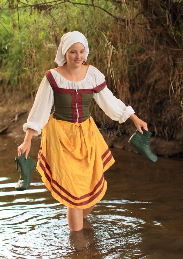 Meisje in historische kleding in water stock afbeelding