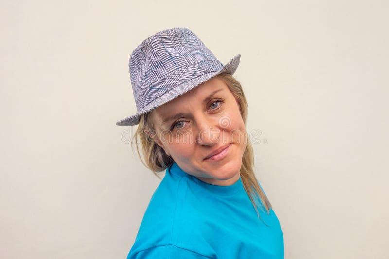 Meisje in hoed De witte midden oude vrouw bekijkt camera en glimlacht Profielportret met gedraaid hoofd en positief gezicht stock fotografie