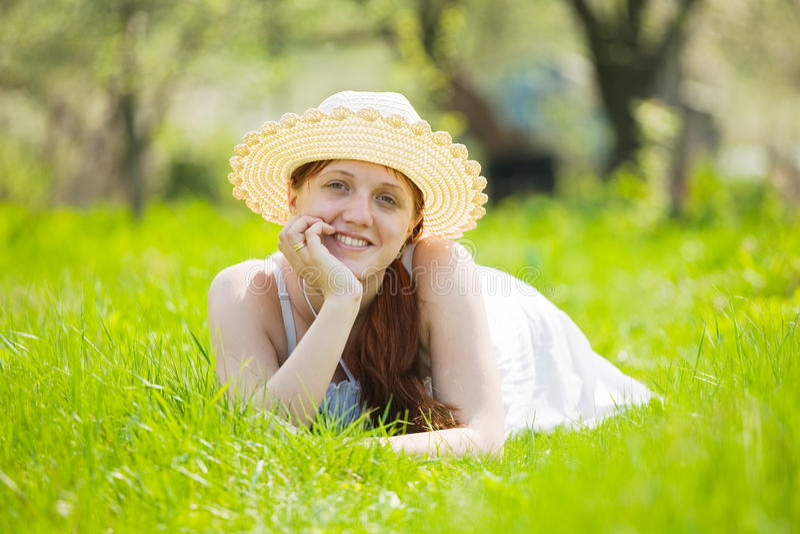 Meisje in hoed die op gras ligt royalty-vrije stock afbeelding