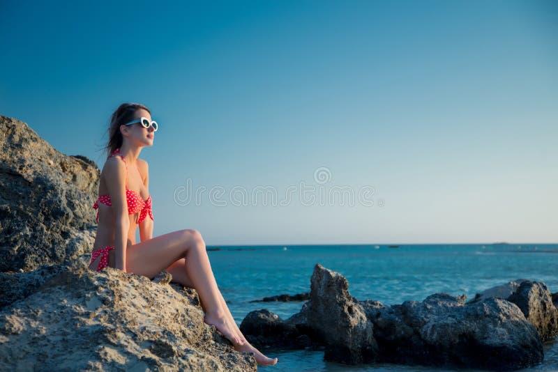 Meisje in hoed en bikini op Elafonissi-rotsstrand stock afbeeldingen