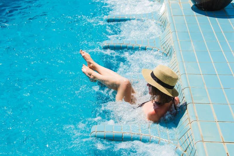 Meisje in hoed het ontspannen in de Jacuzzi van het kuuroord zwembad, die van vakantie genieten Luxutylevensstijl, gezonde voeten stock afbeeldingen