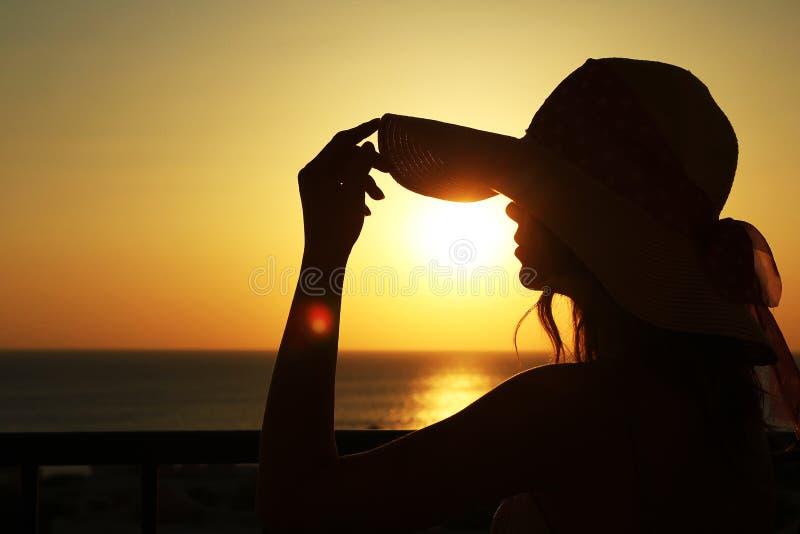 Meisje in hoedensilhouet op het overzees stock afbeeldingen