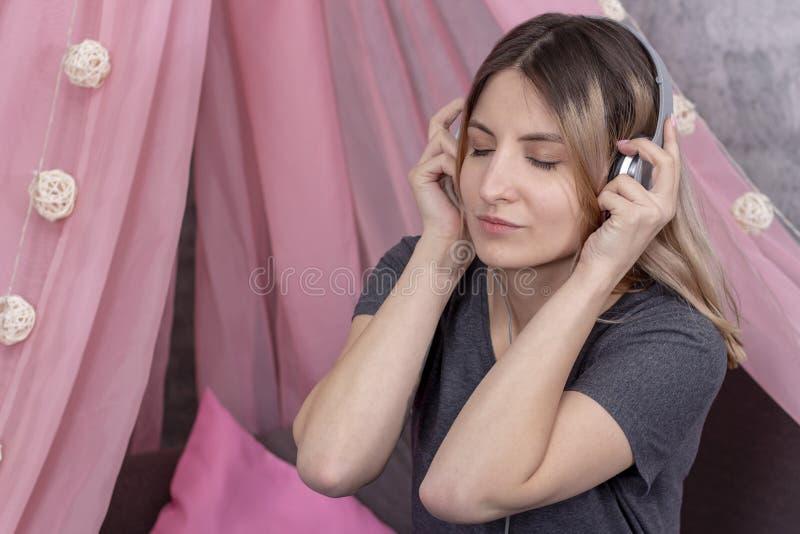 Meisje in hoofdtelefoons die aan muziek luisteren en van het glimlachen genieten stock foto's