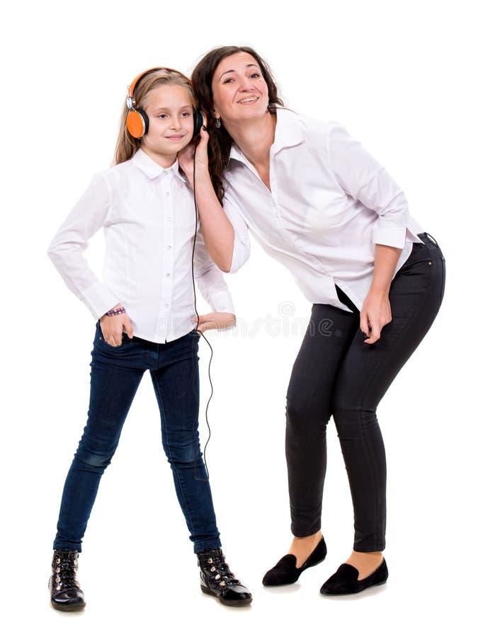Meisje in hoofdtelefoons en haar moeder stock fotografie