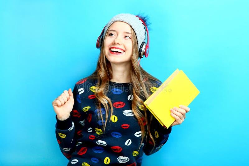 Meisje in hoofdtelefoons met boek royalty-vrije stock foto's