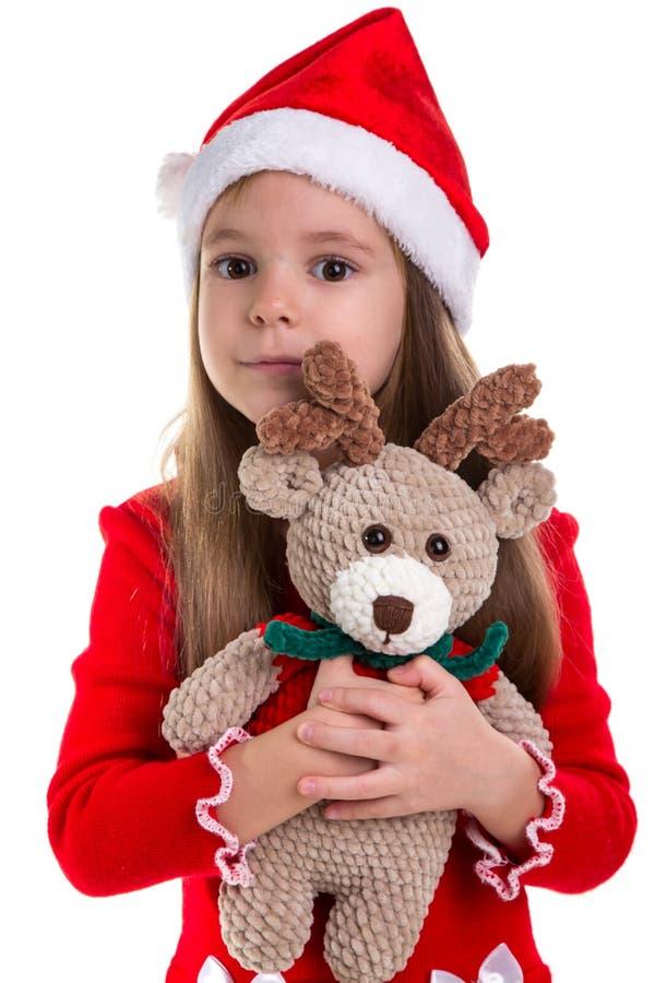 Meisje huggs het herten zachte stuk speelgoed, die een santakostuum dragen over een witte achtergrond wordt geïsoleerd royalty-vrije stock fotografie