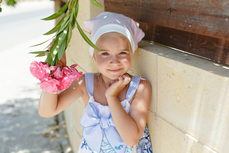 Meisje 5 jaar blonde die een bloem in de zomer ruiken royalty-vrije stock afbeelding