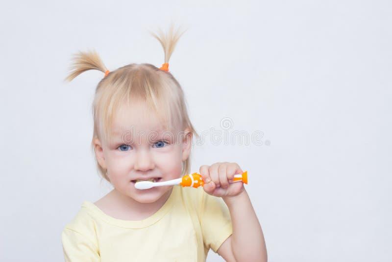 Meisje 2 jaar het oud met vlechten op haar haar borstelt haar tanden en onderzoekt de camera, exemplaarruimte, gezicht stock foto's