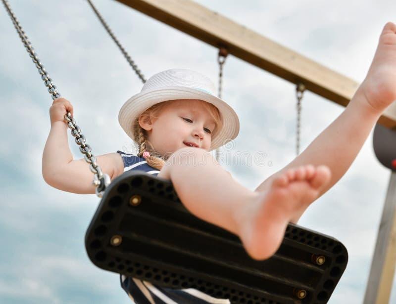 Meisje 3 jaar het oude berijden op een schommeling stock foto