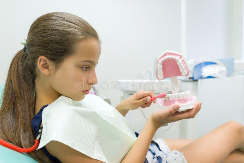 Meisje 10 jaar oud als tandvoorzitter, met tandenborstel Geneeskunde, Tandheelkunde en Gezondheidszorgconcept stock foto's
