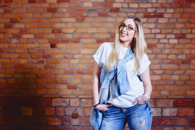 meisje in jeans bij achtergrond van bakstenen muur royalty-vrije stock foto's