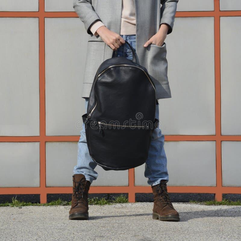 Meisje in jeans, bruine laarzen en een grijze blazer die een grote zwarte leerrugzak, rugzak voor haar houden royalty-vrije stock afbeeldingen
