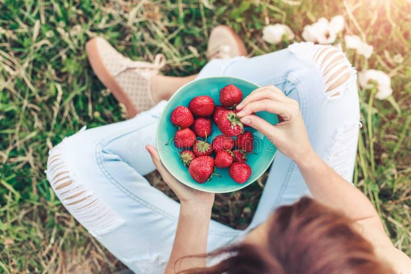 Meisje in jeans die in de zomergras zitten en een plaat van aardbeien houden royalty-vrije stock foto