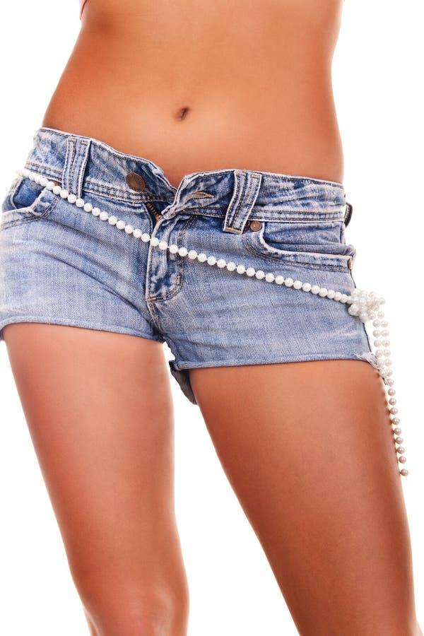 Meisje in jeans met een riem van parels stock foto's