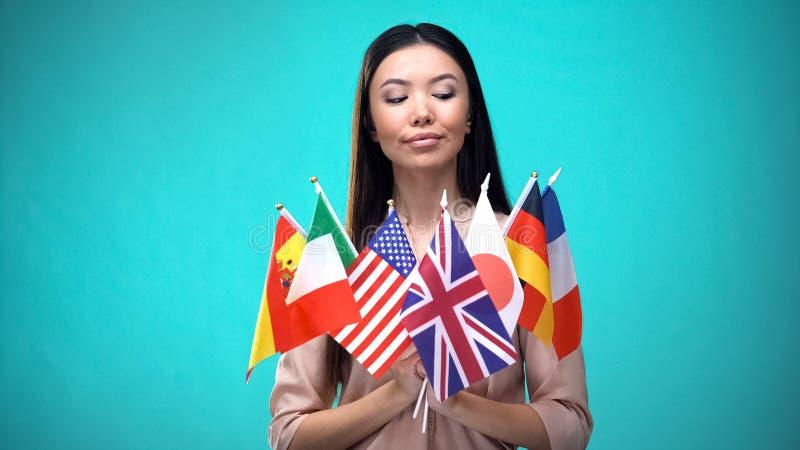 Meisje kijkt naar vlaggen in haar handen, internationaal studentenuitwisselingsprogramma royalty-vrije stock foto's