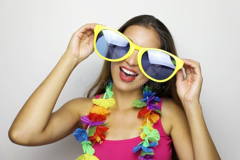 Meisje klaar voor Carnaval-partij De jonge vrouw met grote grappige zonnebril en Carnaval-de slinger glimlachen bij camera op gri royalty-vrije stock fotografie