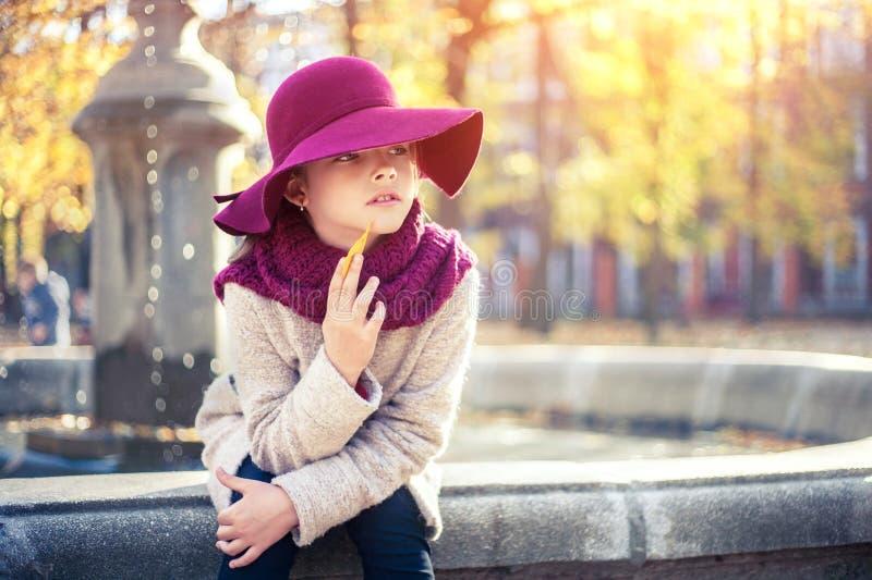 Meisje in klassieke laag en hoed in de herfstpark dichtbij de fontein De herfstseizoen, manier, kinderjaren stock afbeelding