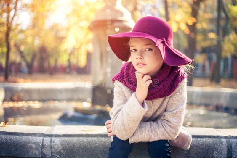 Meisje in klassieke laag en hoed in de herfstpark dichtbij de fontein De herfstseizoen, manier, kinderjaren stock afbeeldingen
