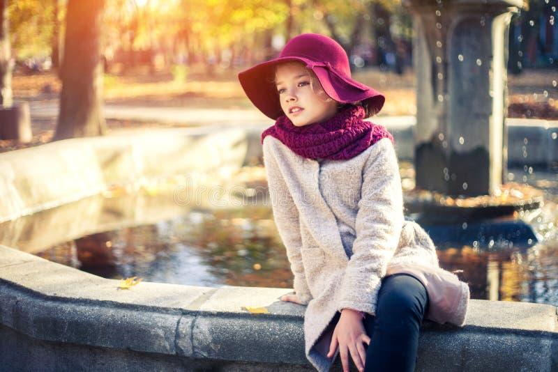 Meisje in klassieke laag en hoed in de herfstpark dichtbij de fontein De herfstseizoen, manier, kinderjaren stock fotografie