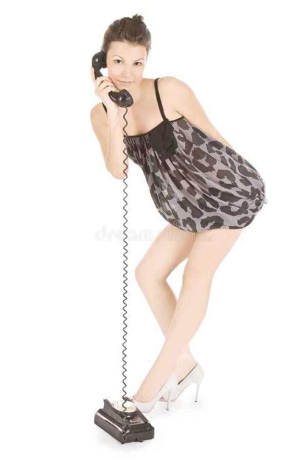 Meisje in kleding die bij de telefoon roept stock foto's