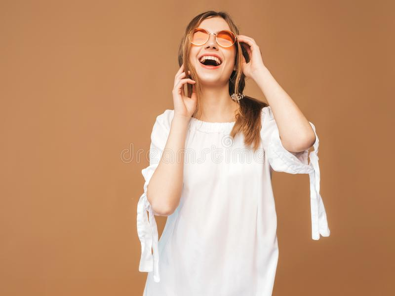 Meisje in kleding van de zomer de witte hipster Het model stellen op gouden achtergrond in zonnebril royalty-vrije stock afbeelding