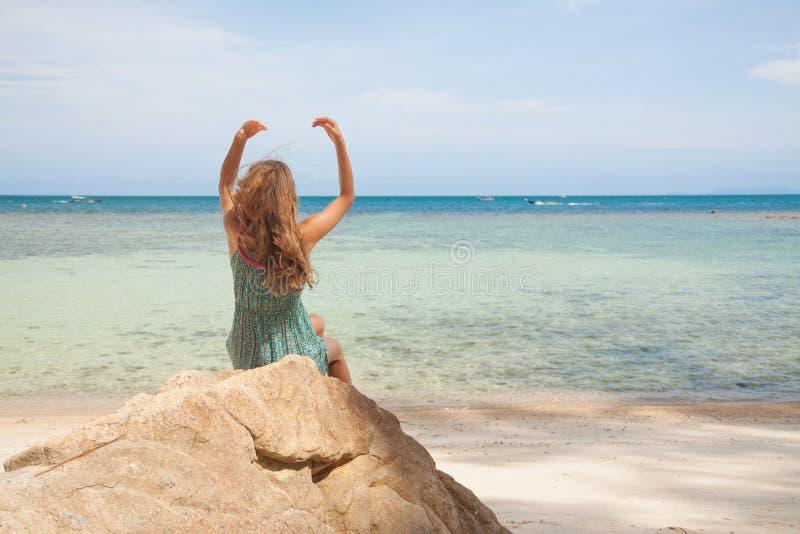 Meisje in kledingszitting op een rots door het overzees stock foto