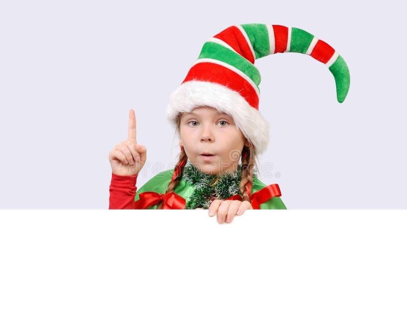 Meisje in kostuum van Kerstmiself met de banner stock foto's