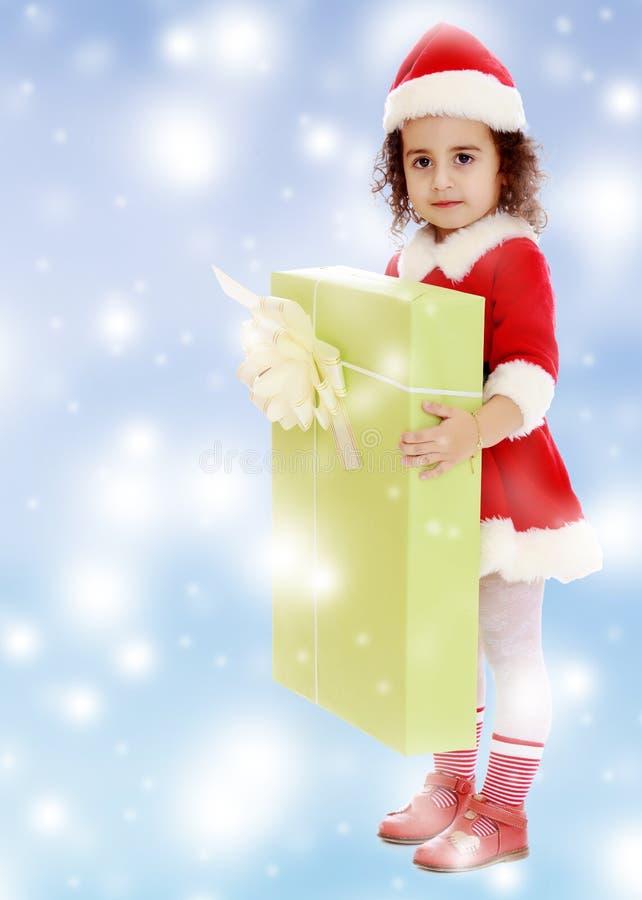 Meisje in kostuum van Santa Claus met gift stock fotografie