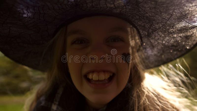 Meisje in kwaad heksenkostuum die camera doen schrikken, vierend Halloween-partij royalty-vrije stock foto