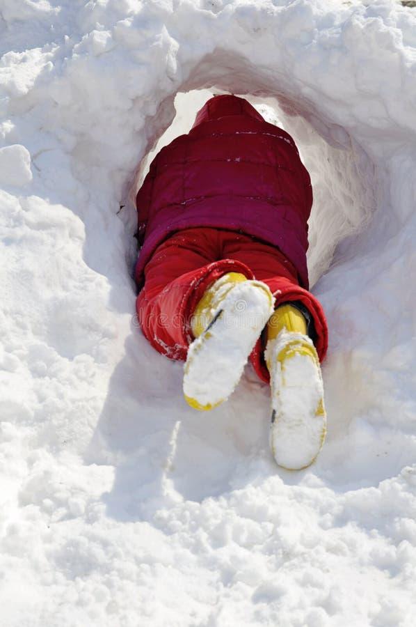 Meisje maakt tunnel in sneeuw stock foto's