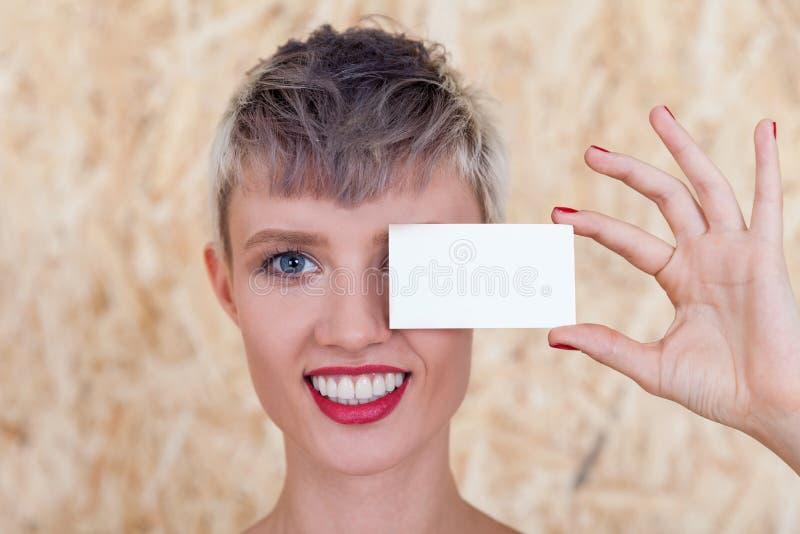 Meisje met adreskaartje dichtbij oog stock afbeeldingen