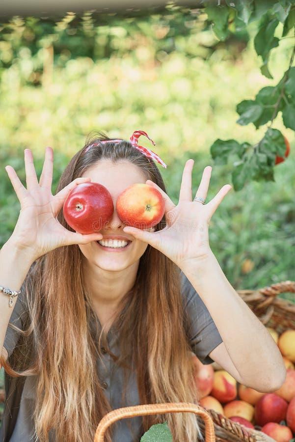 Meisje met Apple in de Apple-Boomgaard Mooi Meisje die Organisch Apple in de Boomgaard eten Het concept van de oogst De herfst ve stock foto's