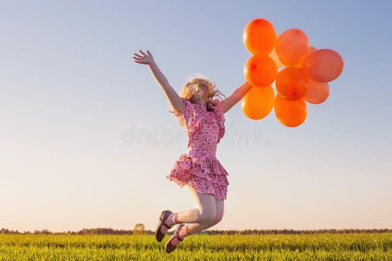 Meisje met ballons het springen royalty-vrije stock foto's