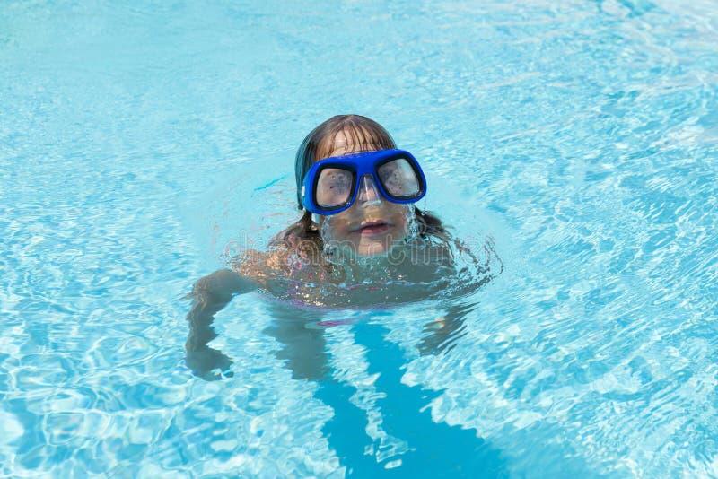 Meisje met blauwe het duiken glazen in een openluchtpool stock fotografie