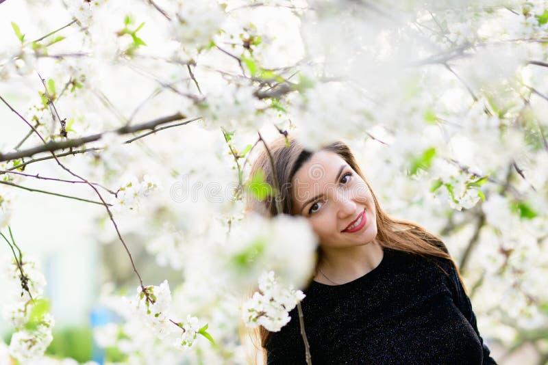 Meisje met bloemen Schitterend model in de de lentetuin meisje dichtbij de boom in de lente Het concept de lente Jonge tuin royalty-vrije stock afbeelding