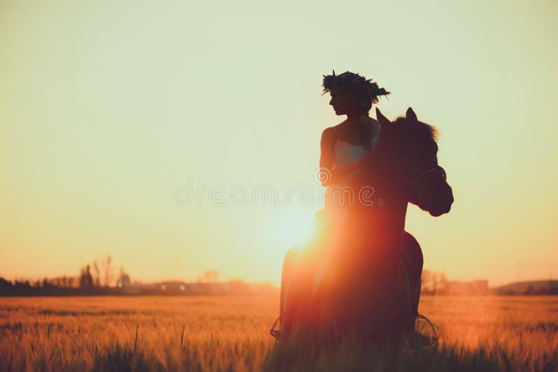 Meisje met bloemen wreathwhile het berijden paard bij zonsondergang stock fotografie