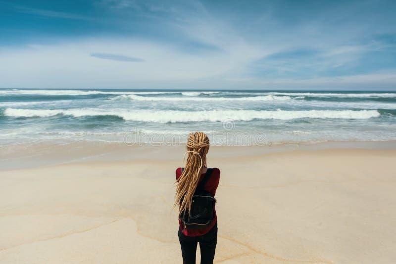 Meisje met blonde die dreadlocks zich op kust bevinden die op de oceaan letten Reis stock fotografie