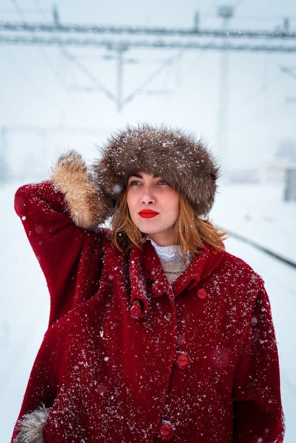 Meisje met bonthoed het stellen in sneeuw royalty-vrije stock fotografie