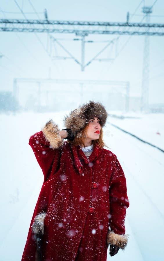 Meisje met bonthoed het stellen in sneeuw stock foto