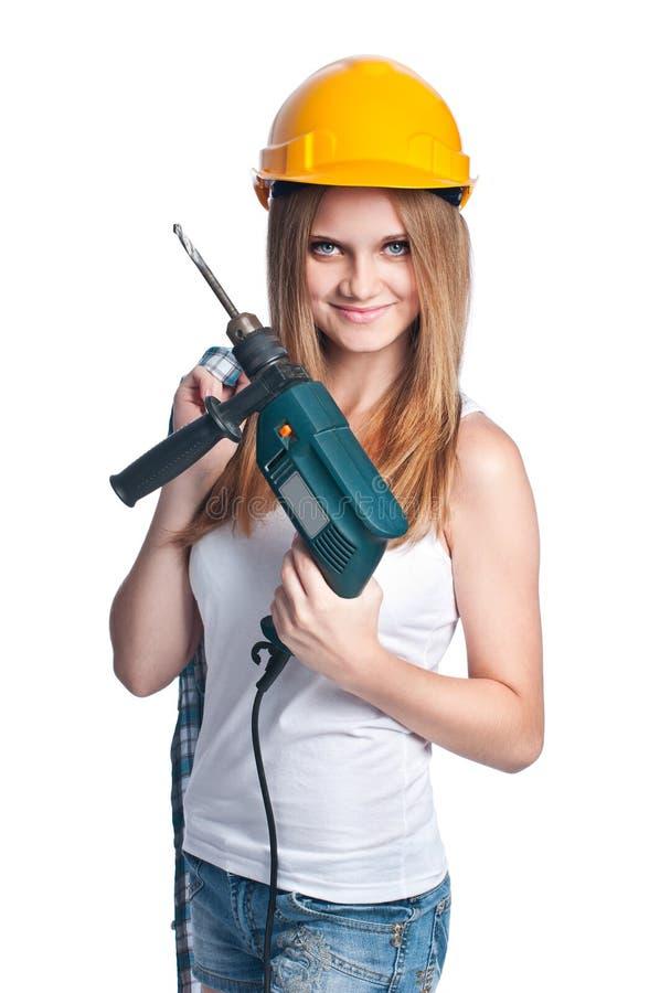 Meisje met boor die gele bouwvakker draagt royalty-vrije stock foto's