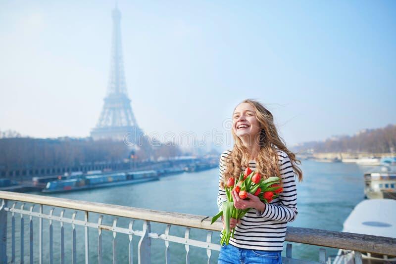 Meisje met bos van rode tulpen dichtbij de toren van Eiffel stock foto