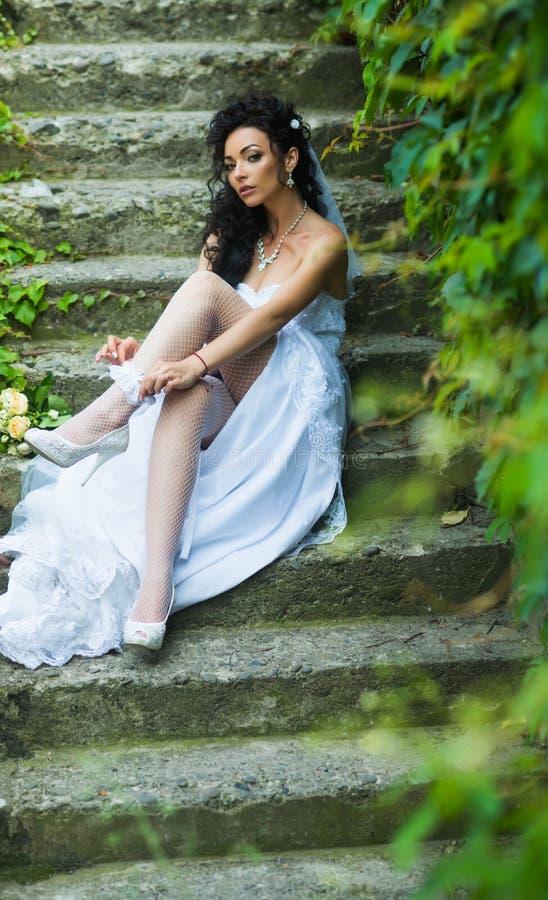 Meisje met bruids make-up en kapsel Het kantkouseband van de vrouwenslijtage op been Sexy vrouw in kousenlingerie op huwelijksdag stock afbeelding