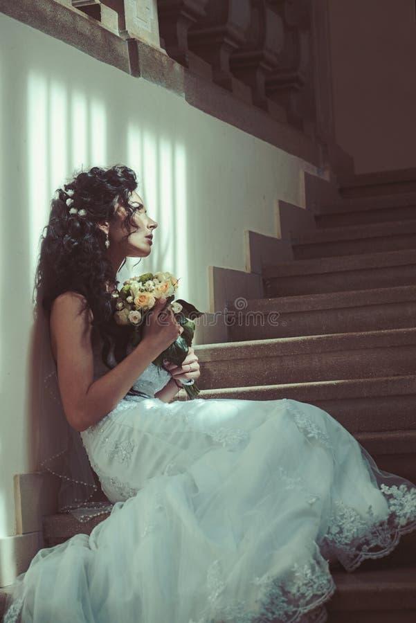 Meisje met bruids make-up en kapsel Sensuele vrouw met huwelijksboeket De vrouw met bloemen zit op trap Bruid binnen stock foto's