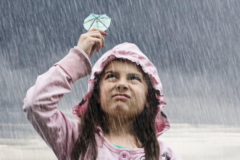 Meisje met cocktailparaplu in de regen stock foto