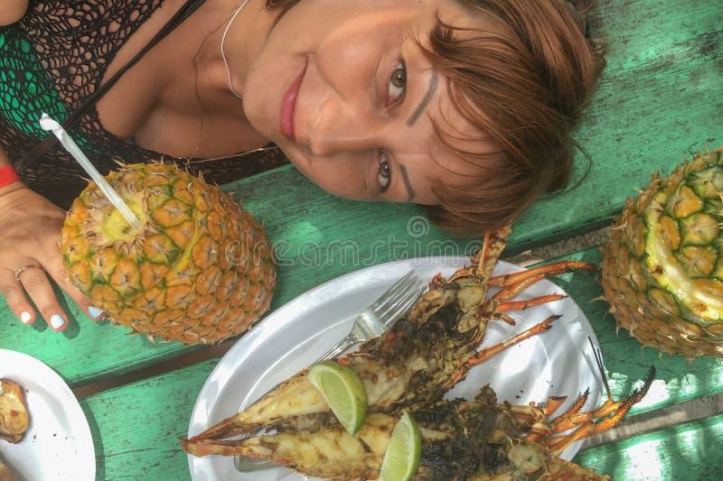 Meisje met de ananas van pinacolada en lijst met zeekreeft Het concept reis stock fotografie