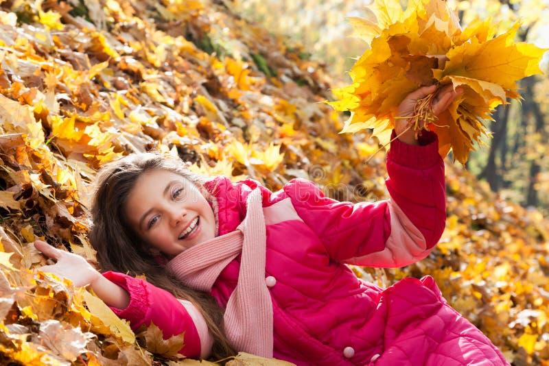 Meisje met de herfstbladeren stock foto's