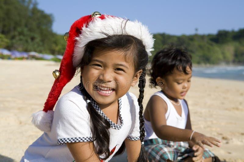 Meisje met de hoed van Kerstmis en jongen op strand stock fotografie