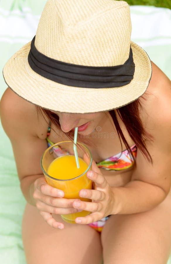 Meisje met de zomerhoed, het drinken jus d'orange stock fotografie