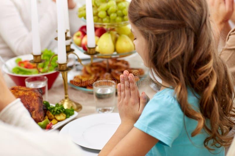 Meisje met diner hebben en familie die thuis bidden royalty-vrije stock fotografie